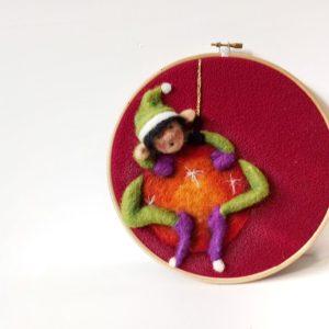 elfo verde di babbo natale su sfera rossa